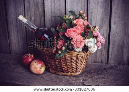 Rustic still life, fresh natural pink roses and a bottle of rose wine with nectarines in a wicker basket on an old wooden barn board background. Flowers and fruits for vintage wedding. - stock photo