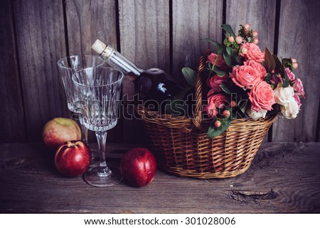 Rustic still life, fresh natural pink roses in a wicker basket  and a bottle of rose wine with two wineglasses and nectarines on an old wooden barn board background. Flowers and fruits for vintage - stock photo