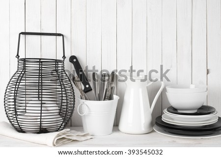 Rustic still life in white and black colors: wire basket with eggs, jug, bucket with cutlery and dishware against white wood wall. - stock photo