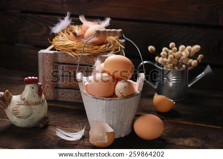 rustic still life with eggs in vintage wooden bucket  and in nest for easter - stock photo