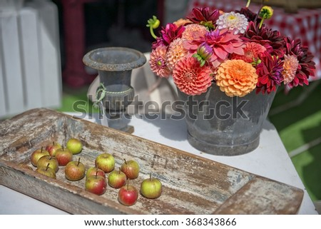 rustic still life with fresh garden flowers and apples on a wooden tray - stock photo