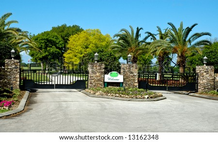 Rustic stone entrance with two electronic iron security gates and welcome sign and stone pillars with rustic lanterns on top. - stock photo