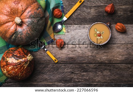 Rustic style pumpkins and soup with seeds and ground cherry on wood. Autumn Season food photo - stock photo