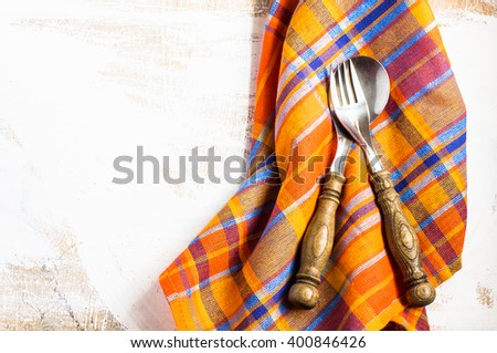 Rustic table setting wit bright napkin, silverware and plate on old wooden table. View from above with copy space - stock photo