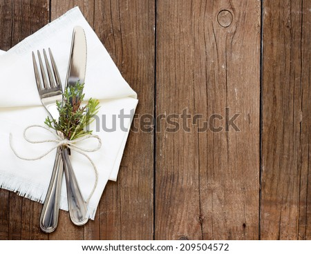 Rustic Table setting with juniper decor on old wooden table - stock photo