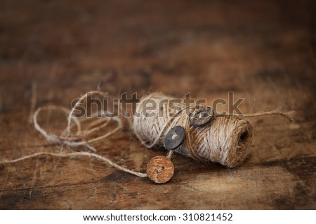 Rustic thread and wood buttons on old farmhouse table - stock photo
