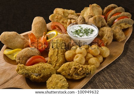 Rustic tray with various meats, cheese balls and garlic sauce - isolated
