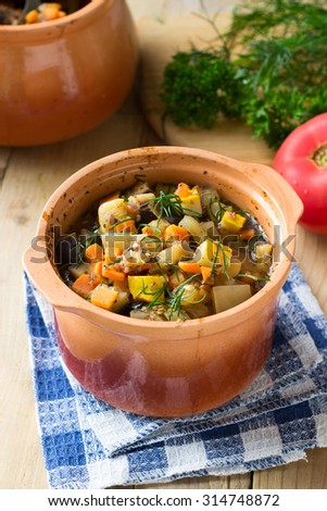 Rustic vegetable dish with eggplants, yellow squash and tomatoes on wooden background