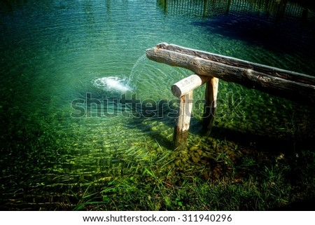 Rustic water feature with water running out of a hollow log into a tranquil pond below in a simple waterfall, high angle view - stock photo