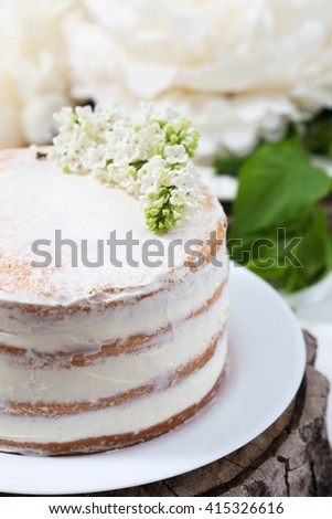 Rustic wedding cake with white flowers, lilac, wooden background, close up, selective focus - stock photo