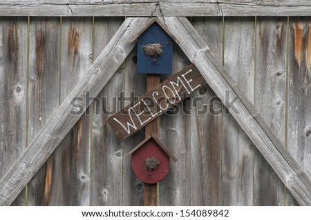 "Rustic ""welcome"" sign displayed on a weathered wooden fence gate."
