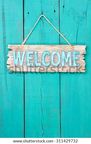 Rustic welcome sign hanging on antique teal blue wooden background - stock photo