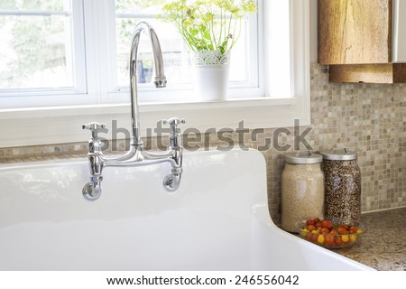 Rustic white porcelain kitchen sink with curved faucet and tile backsplash under large window - stock photo