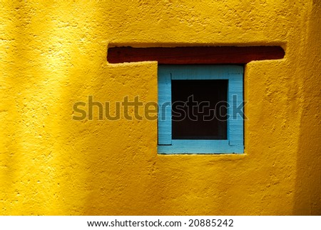 Rustic window in San Miguel de Allende, Spanish colonial town in Mexico. Blue turquoise window on a yellow wall. - stock photo