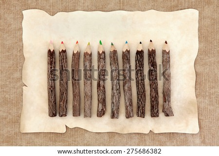 Rustic wood colored pencil set over parchment and brown paper background.