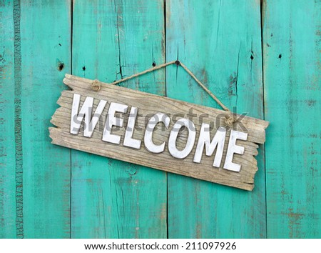 Rustic wood welcome sign hanging on weathered antique blue background - stock photo