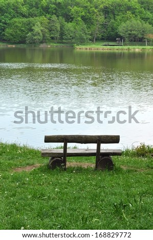Rustic wooden bench near a lake - stock photo