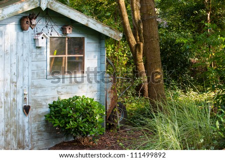 rustic wooden blue old garden shed in countryside - stock photo