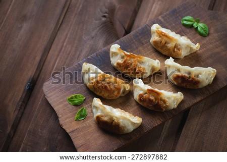 Rustic wooden chopping board with gyoza dumplings, above view - stock photo