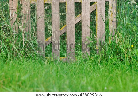 rustic wooden fence in greenery grass  - stock photo