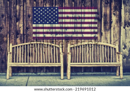 Rustic wooden log benches side by side against a wall of wooden siding with the flag of the United States of America imprinted above the benches.  Filtered for a retro, vintage look.  - stock photo