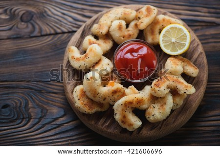 Rustic wooden serving board with fried breaded shrimps