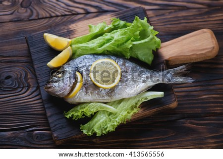 Rustic wooden serving board with whole baked dorado, studio shot - stock photo