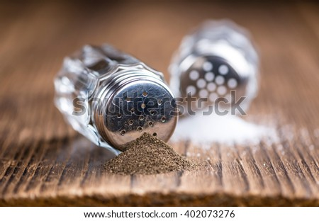 Rustic wooden table with Salt and Pepper Shaker (close-up shot; selective focus) - stock photo