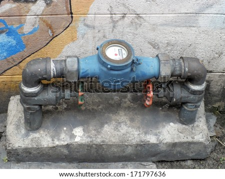 Rusting old water valve with water meter  - stock photo