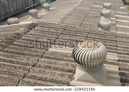 Rusty air ventilator on the roof of factory. - stock photo