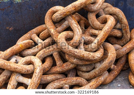 Rusty anchor chain on a pier - stock photo