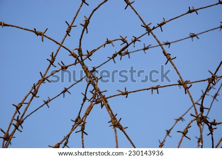 Rusty barbed wire against blue sky. War and imprisonment concepts. Aged photo. - stock photo
