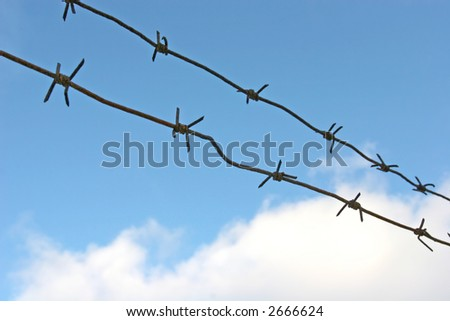 Rusty barbed wire against the cloudy sky