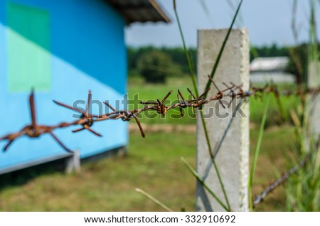 Rusty Barbed wire fence selective focus with blur overgrown grass and blue house background; countryside - stock photo