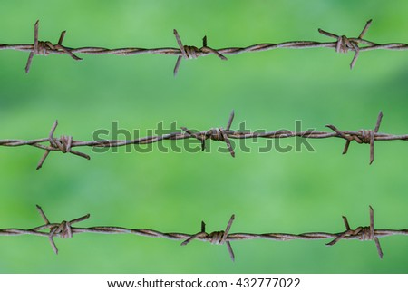 Rusty barbed wire on green background