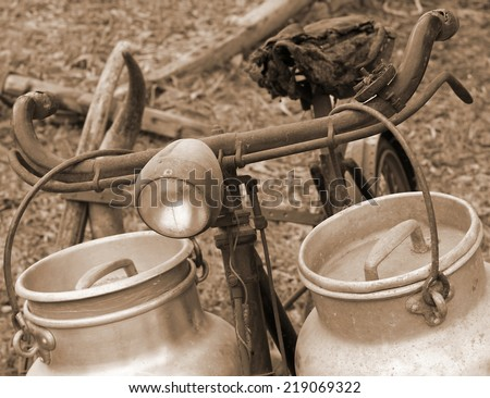 rusty bike of the milkman with old bins for milk sepia - stock photo