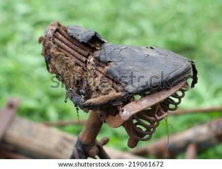 Rusty bike saddle, completely destroyed of the last century - stock photo