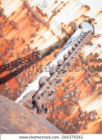 Rusty brown chain. Close up of a rust brown chain of a abandoned boat. - stock photo