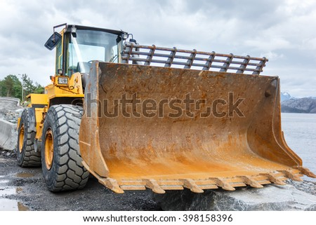 Rusty Bucket Excavator lying on the ground on the construction of the road - stock photo