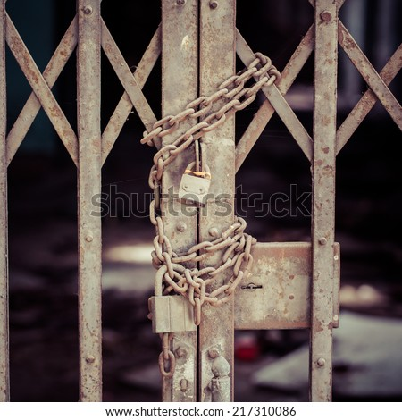 rusty chain and master key locked on grunge iron gate, process color - stock photo