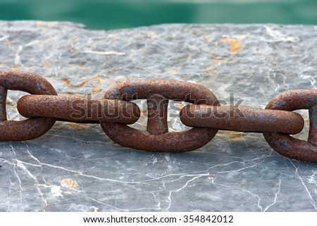 Rusty Chain on a Pier / Close up of a large and rusty chain on a stone background, pier and water - stock photo