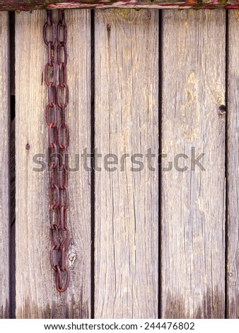 Rusty chain on wood wall with old paint - stock photo