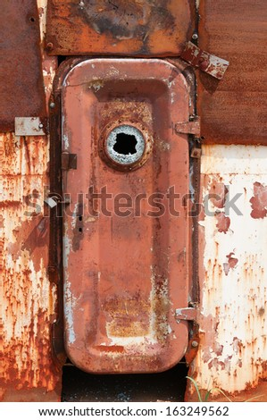 Rusty closed door on metal wall of wrecked abandoned ship