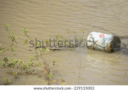 Rusty corroded barrel of toxic industrial chemical liquid dumped in water of river or lake, hazard for natural environment and ecology, copy space. - stock photo