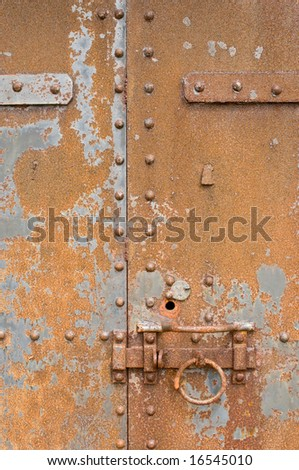 Rusty, corroded old metal door with latch, ring and bolts - stock photo
