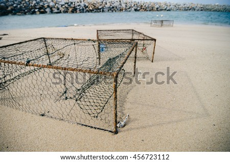 rusty crab pots on the sandy beach over water break background.focus in the middle.shallow depth of field - stock photo
