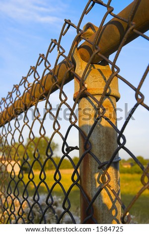 Rusty fence post and chain link fence with blue sky background - stock photo