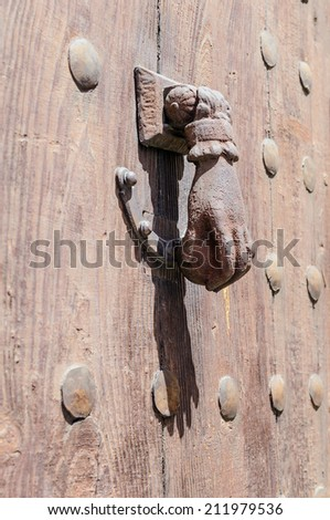 rusty hand shaped knocker in a wooden door - stock photo