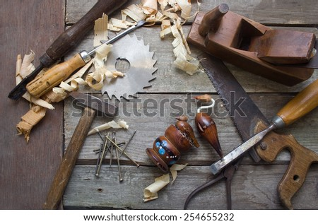 Rusty hand tools table upper view. Old rusty and dirty carpenter`s hand tools lying in a row on wooden table with sawdust and bird statuette. - stock photo