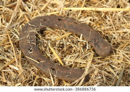 Rusty horseshoe on a straw background - rustic scene in a country style. Old iron Horseshoe - good luck symbol and mascot of well-being in a village house in Western culture. - stock photo
